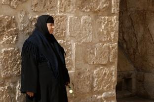 Woman by brick wall in Jerusalem